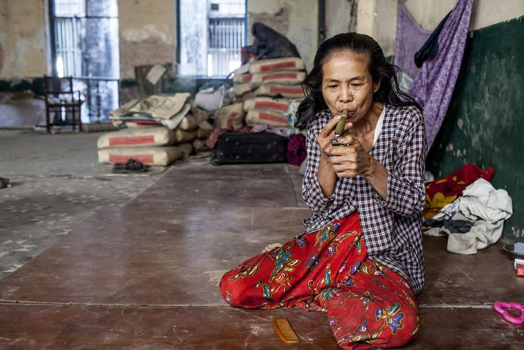 Een vrouw rookt een sigaar in het Lokanat gebouw, ooit de beste plek in Yangon voor Engels snoep, Duits bier en Egyptische sigaretten. Beeld Yvonne Brandwijk