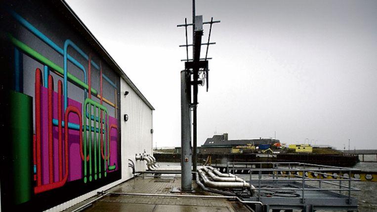 """De eerste zeewaterwarmtecentrale van Nederland staat op de uiterste punt van de haven van Scheveningen. Zeewater is gratis voorhanden en je kunt er warmte aan onttrekken, ook nu de watertemperatuur maar vier of vijf graden is. """"Warmte winnen uit oppervlaktewater kan al decennia. Wij bedachten de truc om er ‿swinters een warmtepomp tussen te zetten‿, zegt Paul Stoelinga van ingenieursbureau Deerns. (Werry Crone/Trouw) Beeld"""