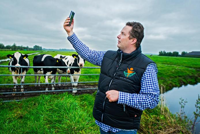 Wisja Pannekoek met zijn mobiel in de polder in het Groene Hart.