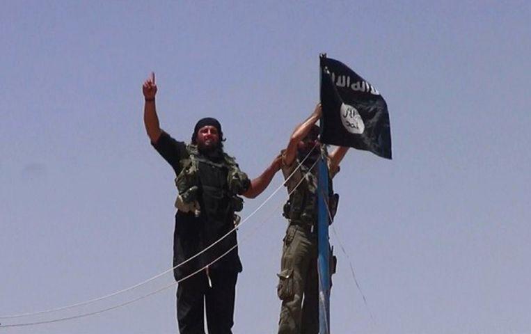 Twee strijders van IS met de vlag van de terreurorganisatie. Beeld AFP