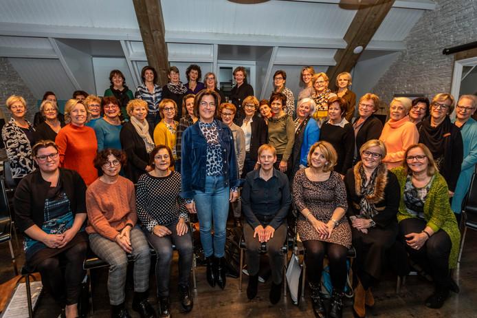 Clubheld Inge Welten (staand) en het Astense koor Vocal Surprise.