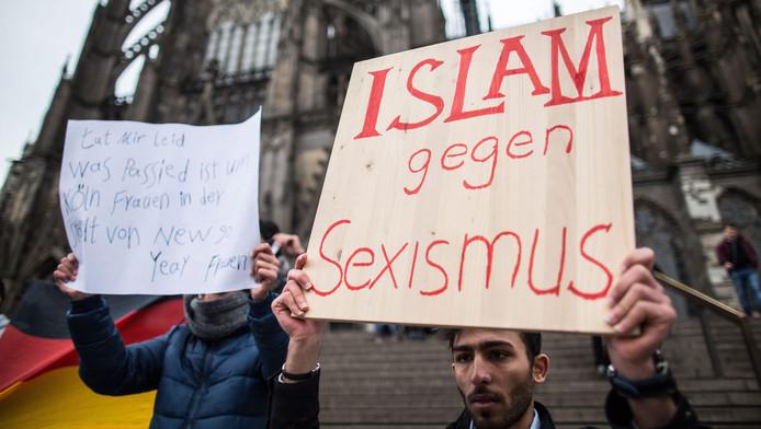 Een Syriër houdt een bord omhoog waarin hij afstand neemt van de aanrandingen in Keulen.