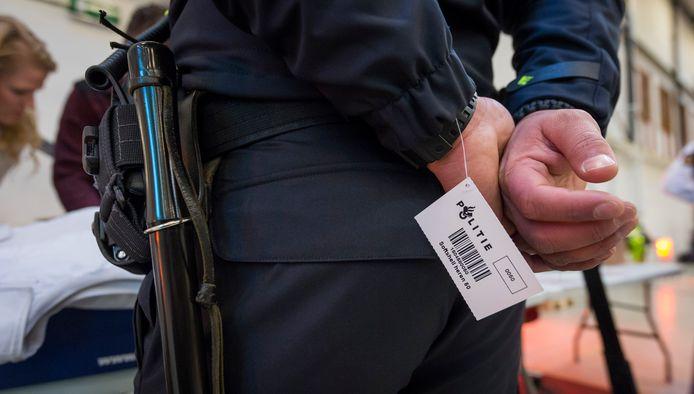 Een Amsterdamse politieman past zijn nieuwe uniform.