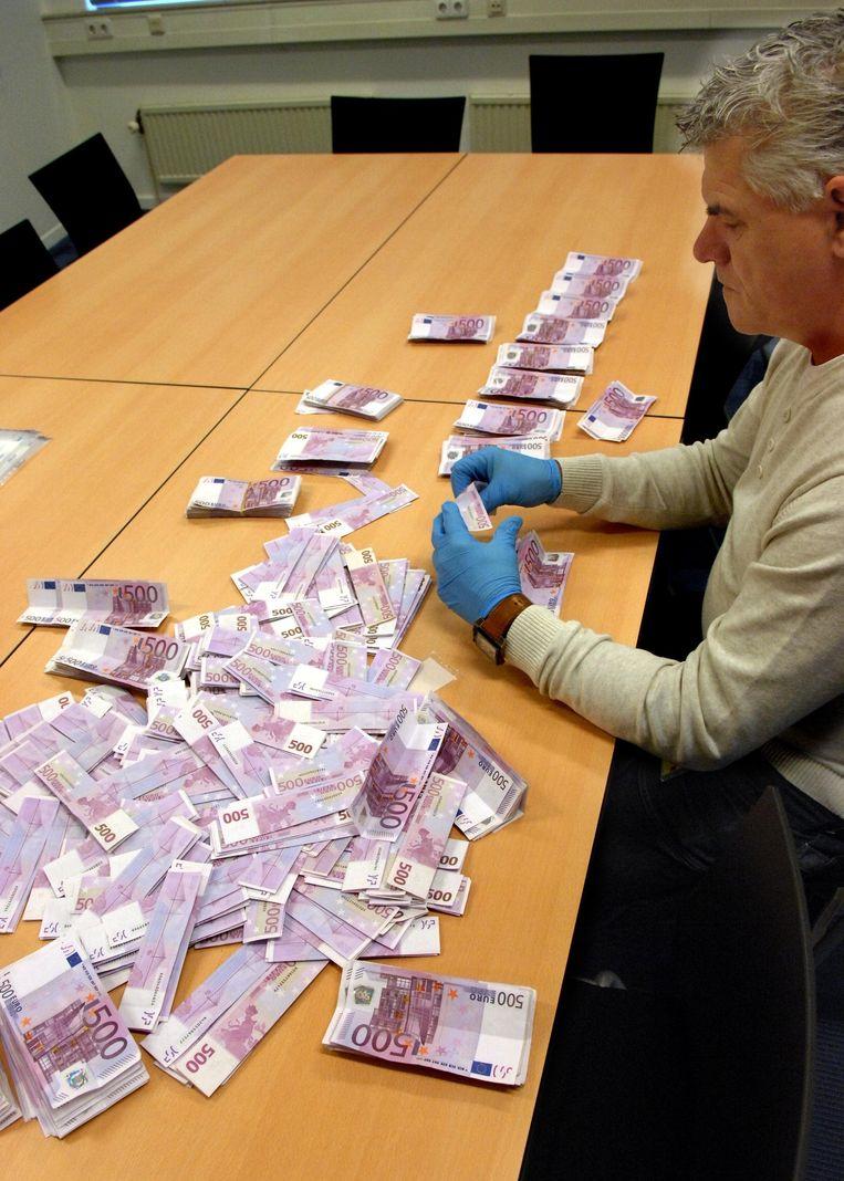 Een rechercheur onderzoekt of er sporen zitten op 500 eurobiljetten. Beeld null