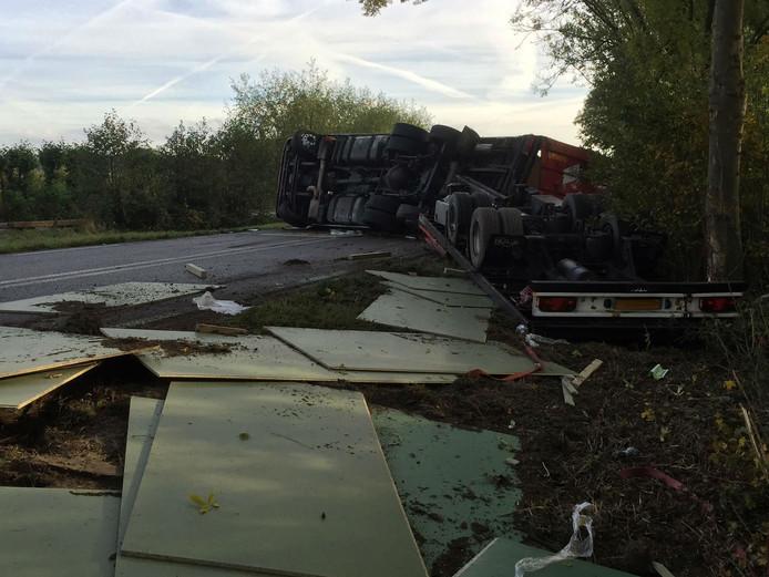 Gekantelde vrachtwagen verliest lading op de N322.