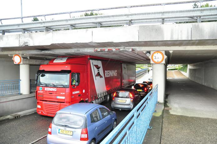 Vrachtwagen zit vast onder viaduct.