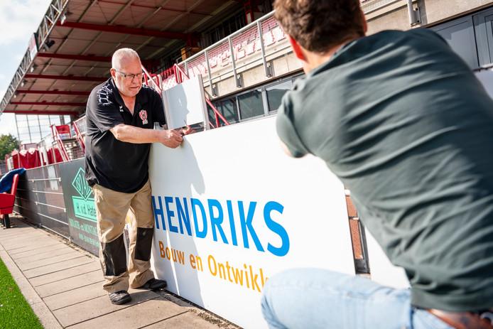 Vrijwilligers van TOP Oss helpen mee met het ophangen van de nieuwe sponsorboarding langs het veld.