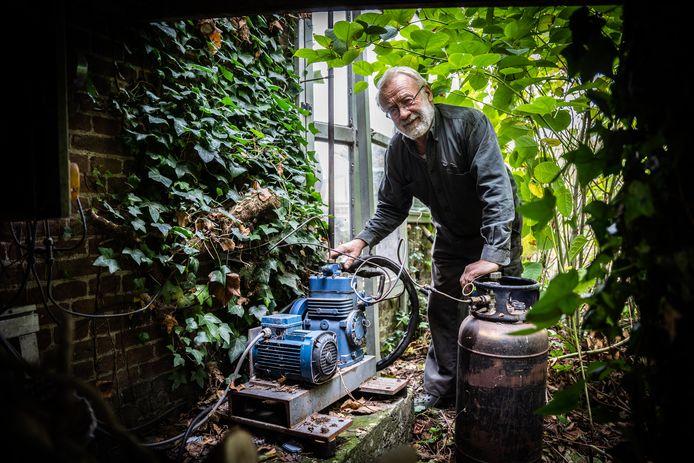 Chris Engel bij de compressor in de tuin, een onderdeel van zijn zelf gemaakte warmtepomp. Foto: Rolf Hensel.