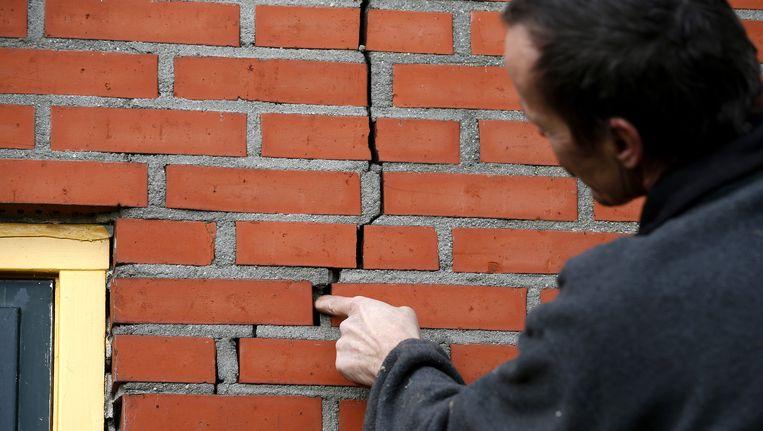 Een bewoner wijst een scheur aan in de muur van zijn woning. Beeld anp
