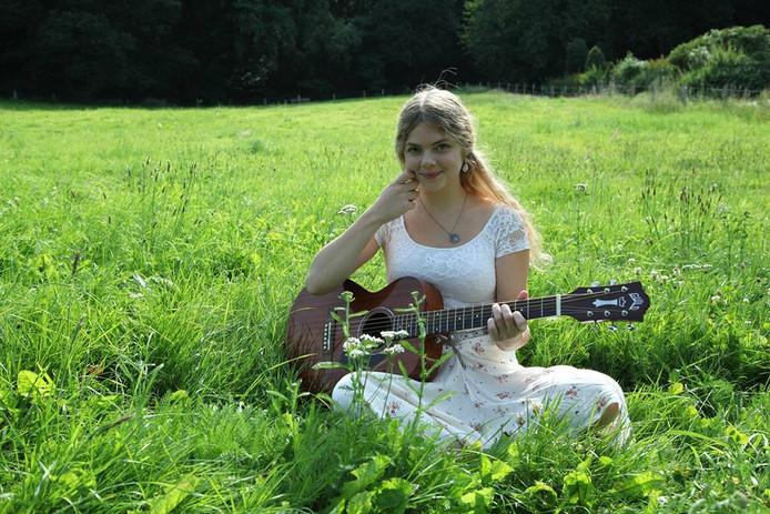 Zangeres Lara Willems treedt op in een tuin.