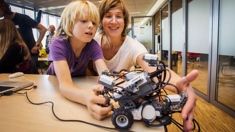 Een moeder en kind programmeren een robot tijdens het Weekend van de Wetenschap. Kinderen op jonge leeftijd leren programmeren draagt bij aan digitale innovatie. Beeld anp