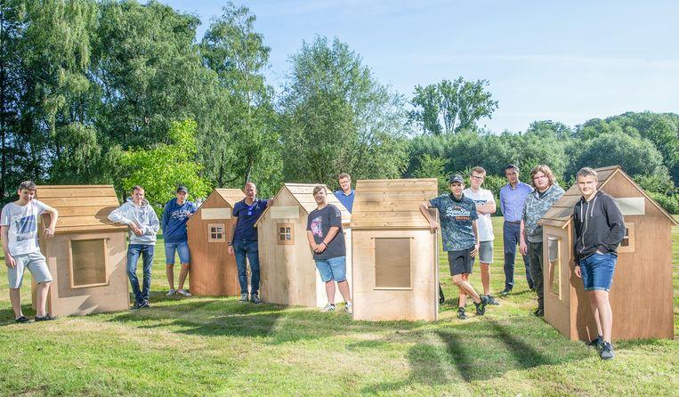 De leerlingen poseren trots bij de huisjes die ze hebben gebouw en die nu de hele provincie zullen rondreizen.