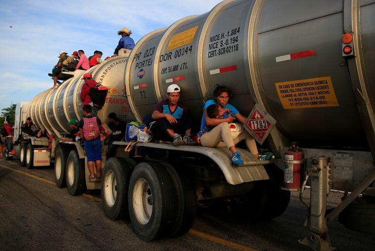 Een vrouw met kind houdt zich vast aan de tanker die rijdt richting Juchitán, Mexico. Beeld AP