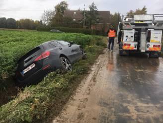 Vrouw glijdt met Mercedes in gracht op weg vol modder