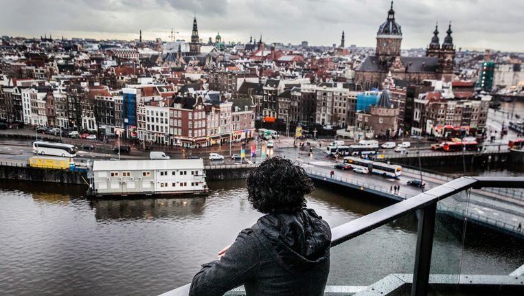 Aziz kijkt uit over Amsterdam waar hij woont en werkt. Beeld Aurélie Geurts