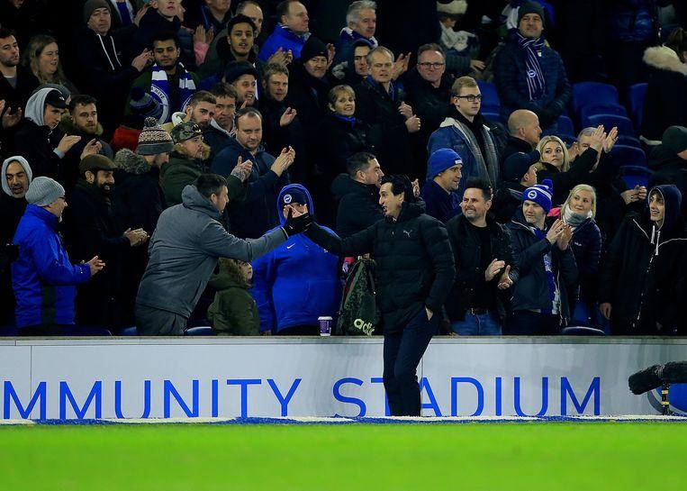 Arsenal-trainer  Unai Emery excuseert zich bij de Brighton & Hove Albion-supporter die hij onbedoeld raakte met de weggetrapte bidon.