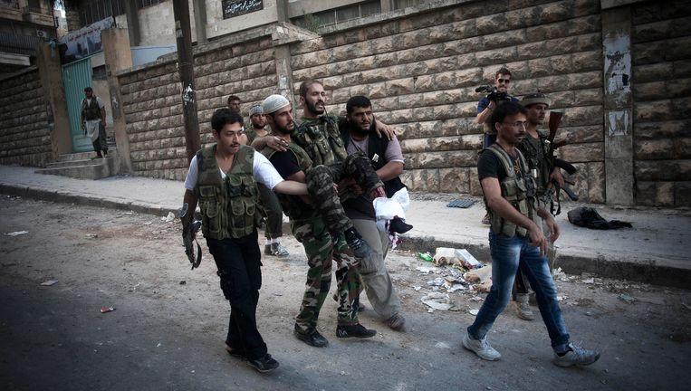 Strijders van het Syrische Vrije Leger dragen een gewonde in de Izaa wijk in Aleppo. Beeld AP