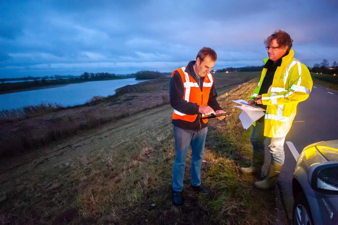 De zogeheten patrouillelopers Geert van Vugt (links) en Gijsbert Smit moeten tijdens de hoogwateroefening een eventuele schade aan de Waaldijk melden. In dit geval die nabij Zuilichem.