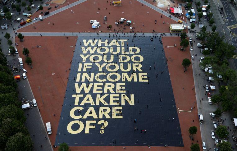 Campagneactie in Genève van de voorstanders van een basisinkomen. Beeld Reuters