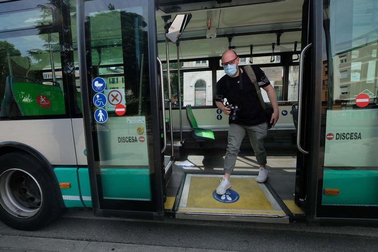 Een man draagt een mondkapje in een bus in Italië.  Beeld EPA