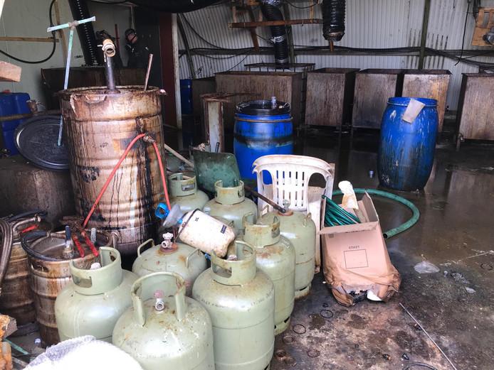In Zaltbommel vond de politie bij de inval een groot drugslab. Er werden onder meer duizenden liters grondstof voor de productie van drugs aangetroffen.