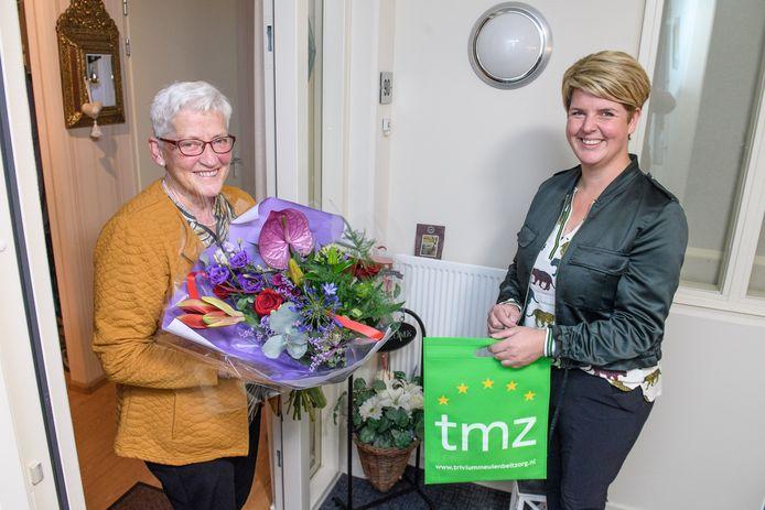 Leydie Lucas (links) wordt verrast met bloemen en een cadeaubon als dank voor 25 jaar vrijwilligerswerk. Rechts Dijkhuismedewerker Martine Veldhof.