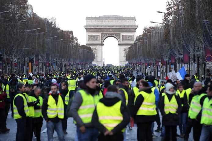 Demonstranten in gele hesjes lopen over de Champs Elysees, waar ze aan het einde worden tegengehouden.