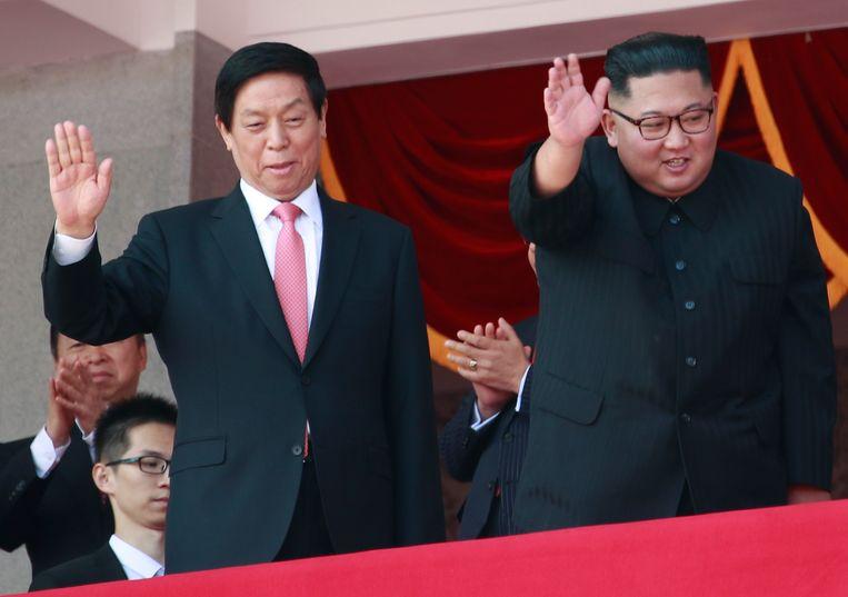 De Noord-Koreaanse leider Kim Jong-un kijkt samen met een hoge Chinese functionaris naar de militaire parade zondag in Pyongyang.  Beeld EPA