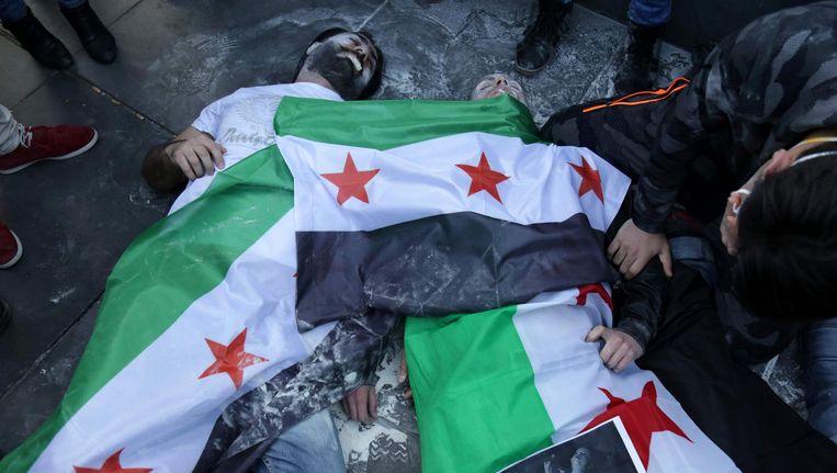 Demonstranten op het Place de la Republique in Parijs, bedekt onder Syrische onafhankelijkheidsvlaggen, bootsen de gevolgen van een gifgasaanval na. Beeld afp
