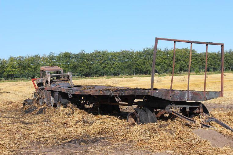 De bobcat en trailer na de brand: helemaal verwoest.