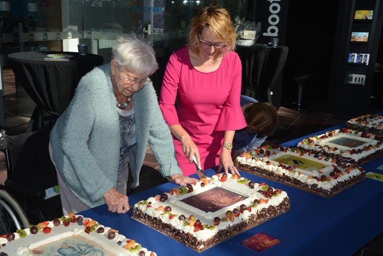 Schepen Anniek Nagels en Adrienne Van Peteghem snijden een taart aan.