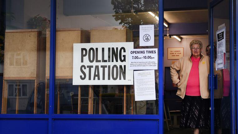 Een stemmer verlaat een stembureau in een wasserette in Oxford. Beeld EPA