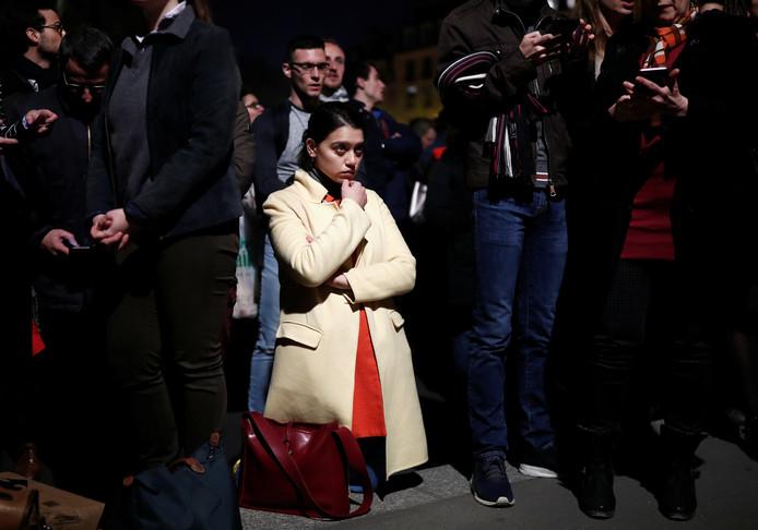 Een vrouw kijkt geknield en in shock naar de brandende Notre-Dame. Op een aantal plekken zochten gelovigen elkaar op, biddend en zingen. Sommige met een rozenkrans in de hand: een gebedsketting die zijn oorsprong vindt in het katholieke geloof.