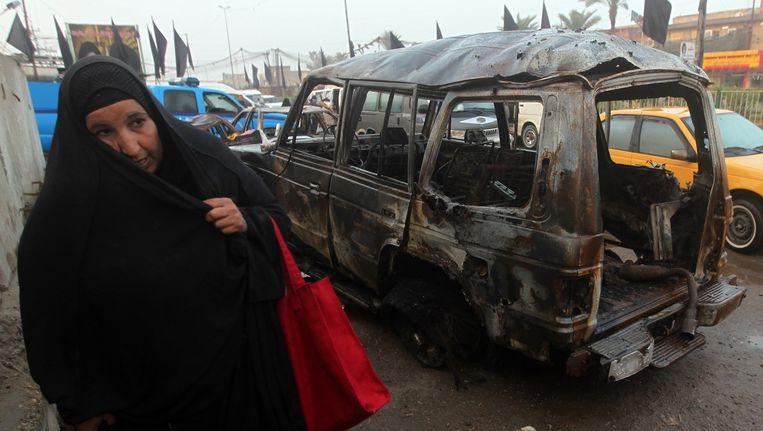 Een vrouw wandelt voorbij het wrak van een bomauto in Bagdad eind november.