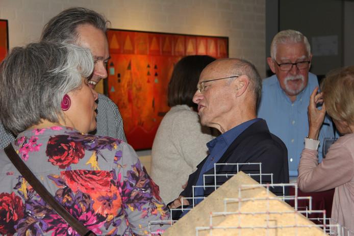 Adriaan van den Berk in een geanimeerd gesprek met zijn gasten tijdens de opening.