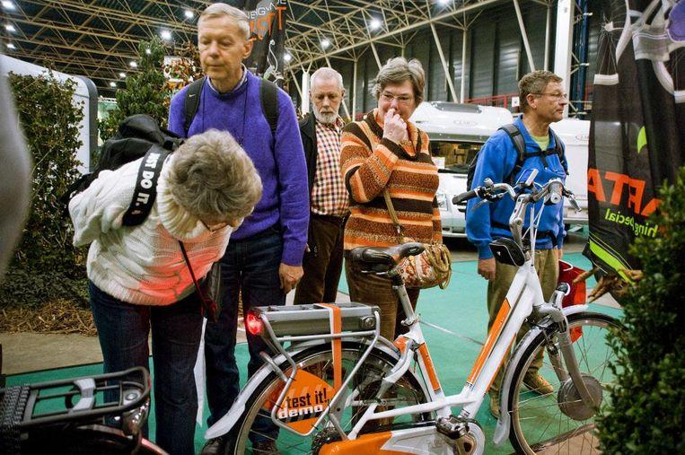 Bezoekers van de vakantiebeurs bekijken een elektrische fiets. Accu's zijn na 3 tot 5 jaar aan vervanging toe, al kunnen ze volgens de ANWB bij goede behandeling 7 jaar mee. Beeld null