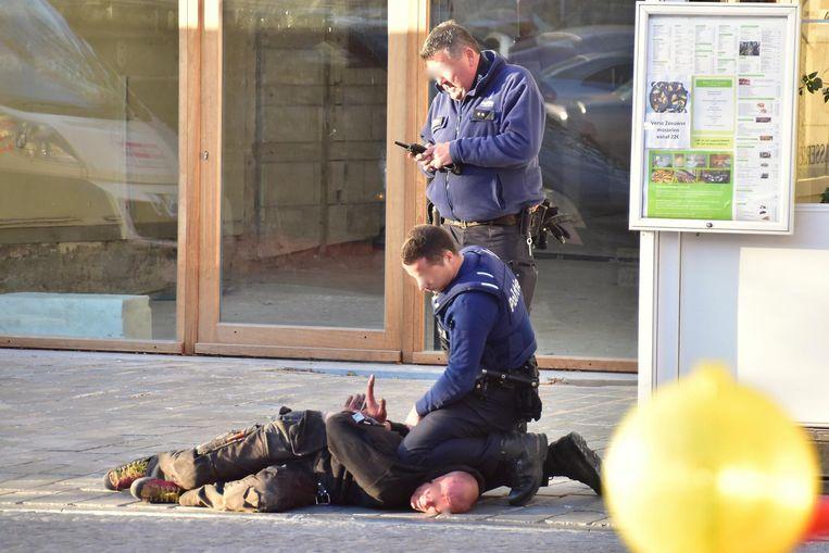 De politie slaat de stomdronken man in de boeien.