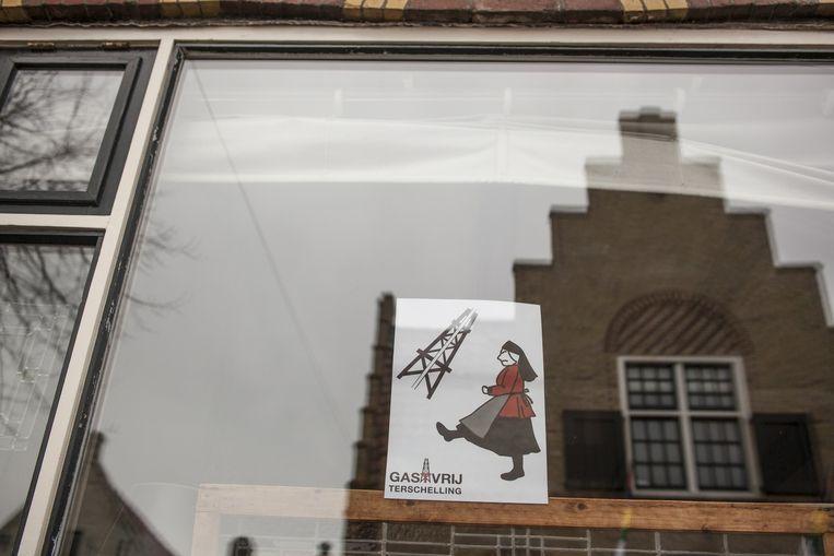 Protest achter de ramen van de Terschellingers tegen gasboringen op het eiland Beeld Harry Cock / de Volkskrant