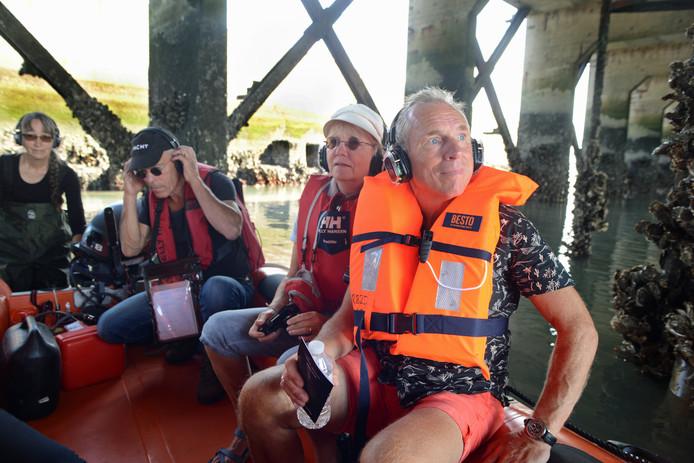 Kunstenaar Anne Ausloos duwt de boot door de verborgen zeetuin in het caisson. Met schipper Bas van Damme en aan boord Marjan en Hans Hidskes uit Serooskerke.