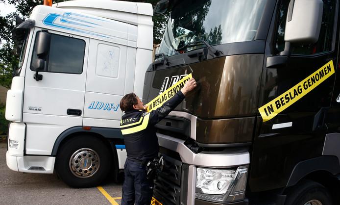 Een agent beplakt één van de elf trucks van het verdachte transportbedrijf met een grote sticker tijdens de inbeslagname van de voertuigen in 2016.