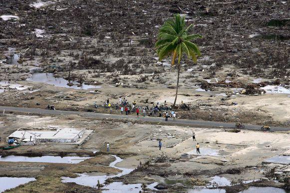 Slachtoffers van een tsunami schuilen onder een palmboom. De rest van het stadje is vernield.
