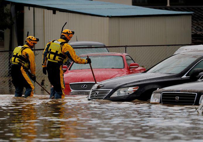 Reddingswerkers doorzoeken een overstroomd gebied.