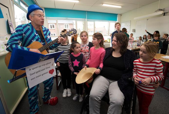 Meester Hans van de Christoffelschool speelt gitaar voor Elma Lamers en alle kinderen.