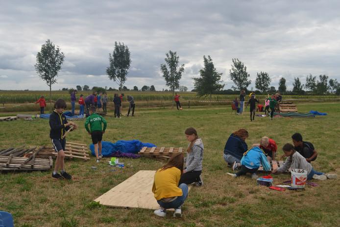 De erste activiteit van het KeLaLo-kamp: hutten timmeren met pallets en platen.