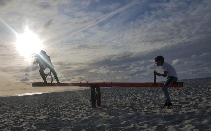 Terwijl de ondergaande zon steeds verder de zee in zakt, vermaken Lucy en Justin zich op het strand bij Domburg op de wip.