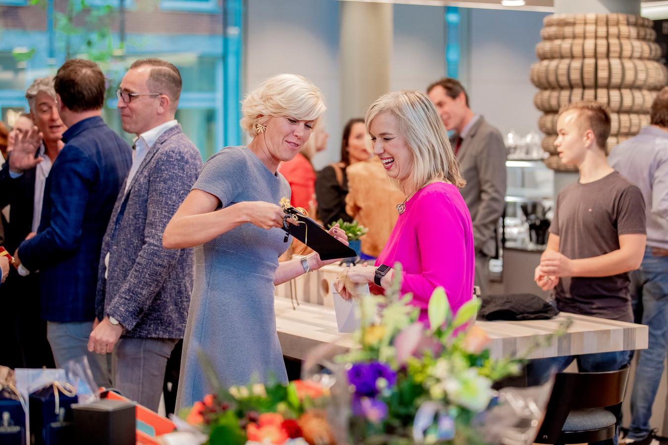 De in het roze gestoken Ilse Harmelink heeft zichtbaar lol tijdens haar afscheid als directeur van Apeldoorn Marketing.