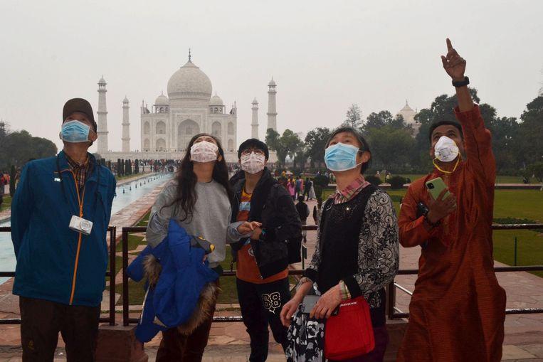 Chinese toeristen met gezichtsmaskers tijdens een bezoek aan de Taj Mahal in India.  Beeld AFP