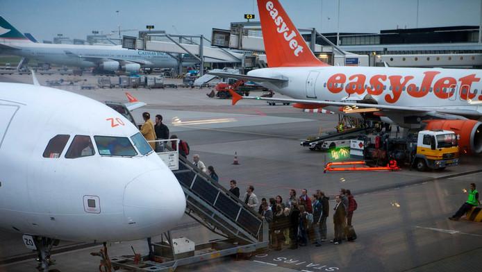 Passagiers stappen bij de H-pier van Schiphol in een toestel van Easyjet