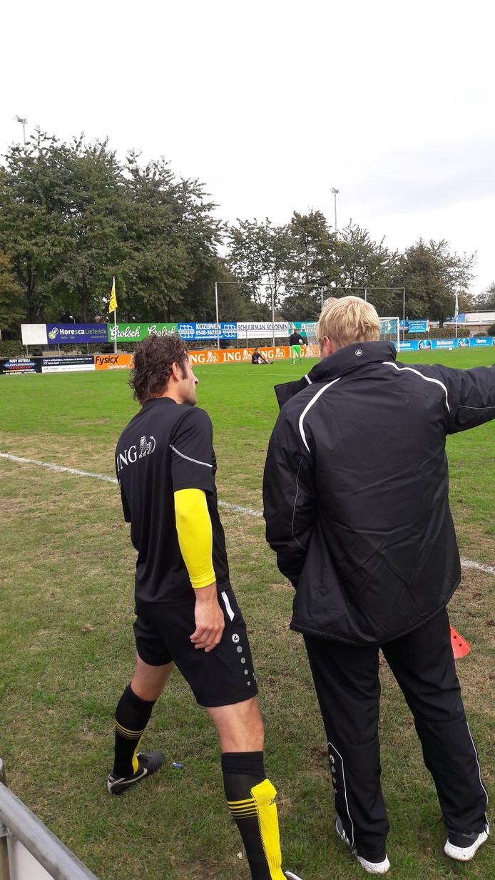 Trainer Toine Rorije en routinier Sander Poll bespreken de strategie voor het duel tegen KOSC.