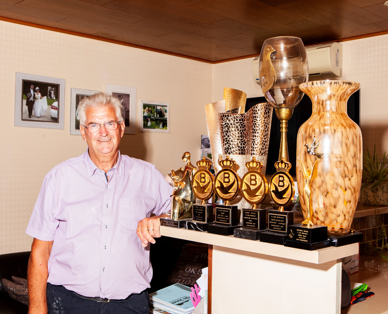 Joël Verschoot in zijn woning in het Belgische Ingelmunster, bij de trofeeën die hij won met zijn duiven. Beeld Hilde Harshagen